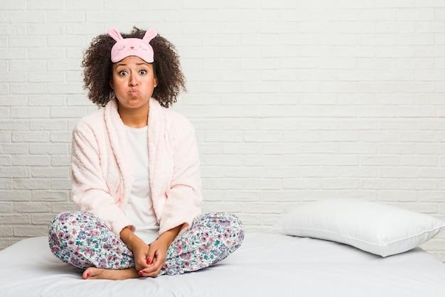 Młoda Amerykanin Afrykańskiego Pochodzenia Kobieta W łóżku Jest Ubranym Pijama Dmucha Policzki, Ma Zmęczonego Wyrażenie. Premium Zdjęcia