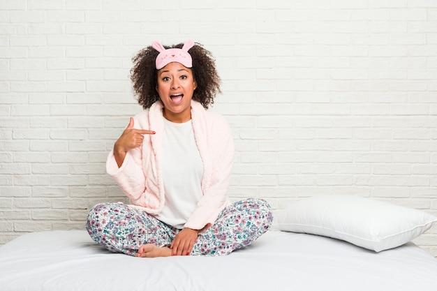 Młoda Amerykanin Afrykańskiego Pochodzenia Kobieta W łóżku Jest Ubranym Pijama Osoby Wskazuje Ręcznie Koszulowa Kopii Przestrzeń, Dumny I Ufny Premium Zdjęcia