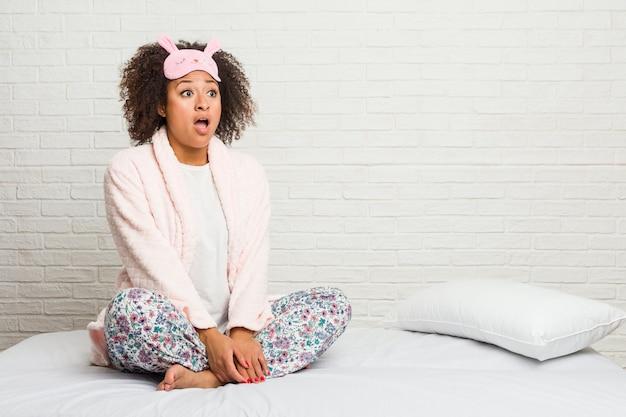 Młoda Amerykanin Afrykańskiego Pochodzenia Kobieta W łóżku Jest Ubranym Pijama Zszokowany Z Powodu Czegoś, Co Widziała. Premium Zdjęcia