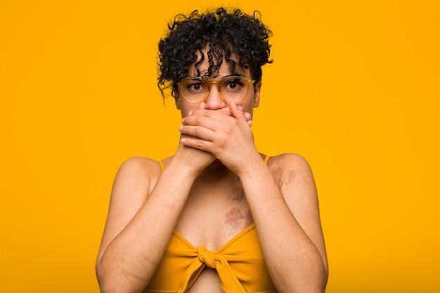 Młoda amerykanin afrykańskiego pochodzenia kobieta z skóry urodzenia szokiem zakrywa usta rękami. Premium Zdjęcia