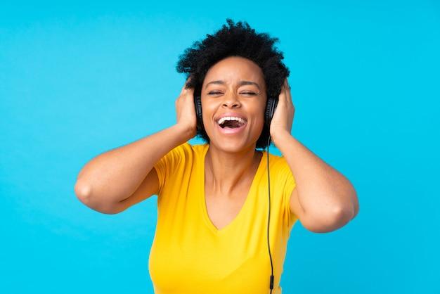 Młoda amerykanin afrykańskiego pochodzenia kobiety słuchająca muzyka z wiszącą ozdobą Premium Zdjęcia