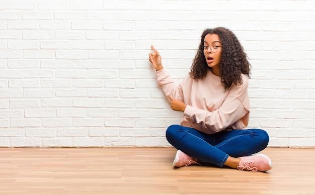 Młoda Amerykanin Afrykańskiego Pochodzenia Murzynka Czuje Zszokowanego I Zaskoczonego Premium Zdjęcia