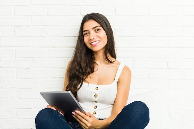 Młoda Arabka Siedzi Na łóżku Za Pomocą Tabletu Premium Zdjęcia
