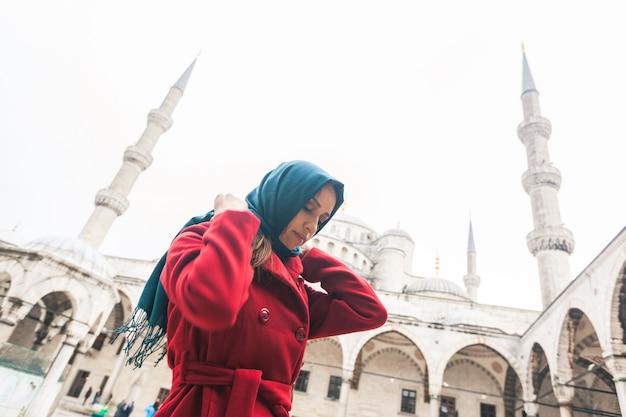 Młoda arabska kobieta jest ubranym przesłonę przed meczetem w istanbuł Premium Zdjęcia