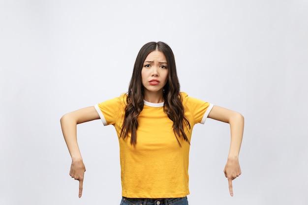 Młoda Atrakcyjna Azjatycka Kobieta, Która Wskazuje Na Palec Z Nieszczęśliwą Emocją Premium Zdjęcia