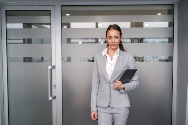 Młoda Atrakcyjna Bizneswoman Kaukaski W Wizytowym Stojąc Przed Salą Konferencyjną I Trzymając Tablet W Rękach. Koncepcja Firmy. Premium Zdjęcia