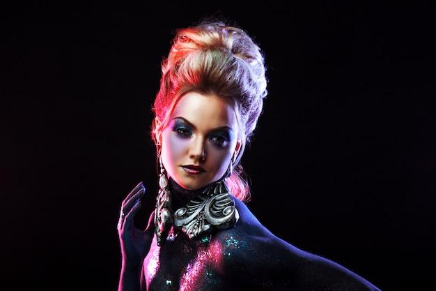 Młoda Atrakcyjna Blondynka W Jasnym Makijażu Artystycznym, Wysokich Włosach, Malowaniu Ciała. Dłoń Na Twarzy Premium Zdjęcia