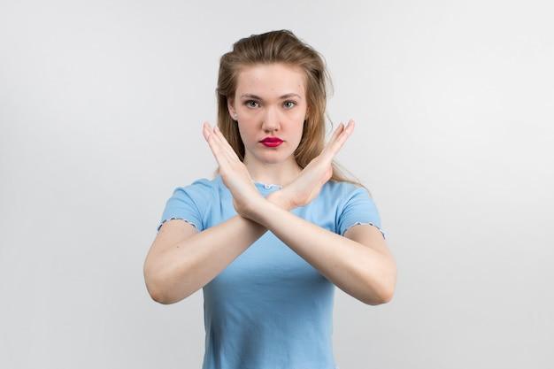 Młoda Atrakcyjna Dziewczyna W Niebieską Koszulę I Piękne Włosy Pokazując Znak Stopu Darmowe Zdjęcia