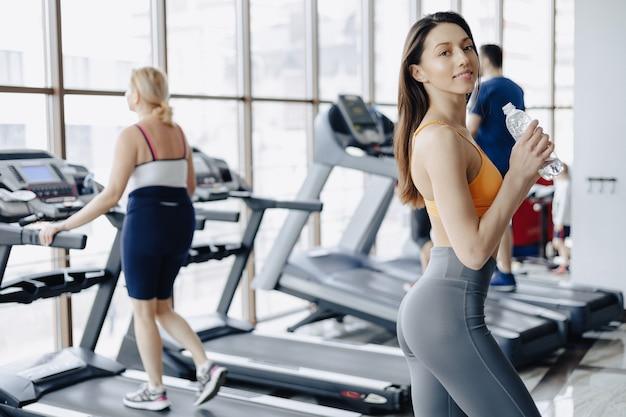 Młoda atrakcyjna dziewczyna w wody pitnej siłowni na tle bieżni Premium Zdjęcia