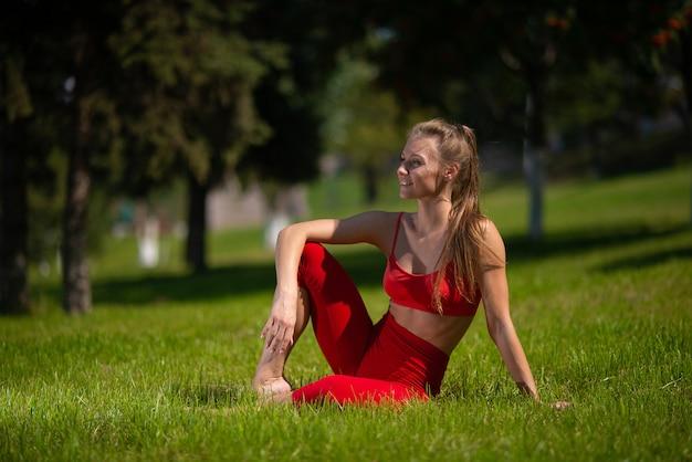 Młoda atrakcyjna kobieta ćwiczy joga outdoors. dziewczyna wykonuje różne ćwiczenia na trawie Premium Zdjęcia