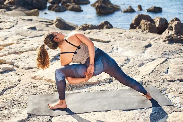 Młoda Atrakcyjna Kobieta ćwiczy Jogę W Pozie Związanej Kąt Boku Na Plaży. Premium Zdjęcia