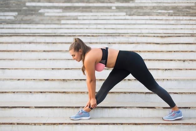 Młoda Atrakcyjna Kobieta Plus Size W Sportowej Bluzce I Legginsach Rozciągająca Się Na Schodach Podczas Spędzania Czasu Na świeżym Powietrzu Premium Zdjęcia