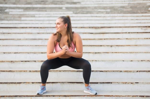 Młoda Atrakcyjna Kobieta Plus Size W Sportowej Bluzce I Legginsach Uprawia Sport Na Schodach, Radośnie Patrząc Na Zewnątrz Premium Zdjęcia
