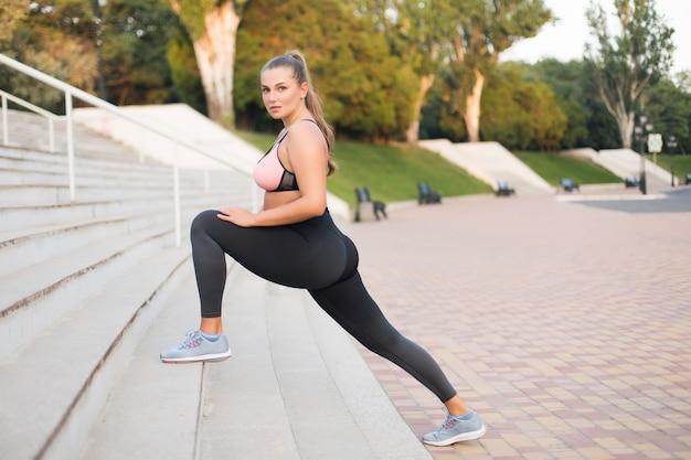 Młoda Atrakcyjna Kobieta Plus Size W Sportowej Bluzce I Legginsach W Zamyśleniu Rozciągająca Się Na Schodach W Parku Miejskim Premium Zdjęcia