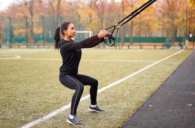 Młoda Atrakcyjna Kobieta Robi Trening Zawieszenia Z Paskami Fitness Na świeżym Powietrzu Premium Zdjęcia