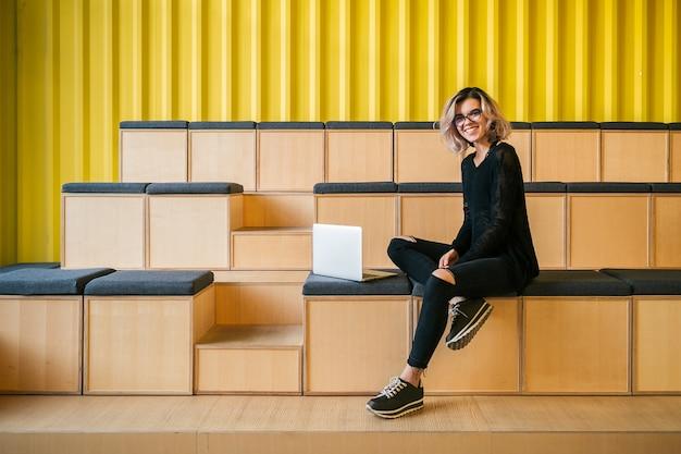 Młoda Atrakcyjna Kobieta Siedząca W Sali Wykładowej, Pracująca Na Laptopie, W Okularach, Nowoczesne Audytorium, Edukacja Studencka Online, Freelancer, Uśmiechnięta, Nastoletni Startup Darmowe Zdjęcia