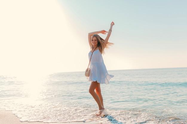 Młoda Atrakcyjna Kobieta Szczęśliwa Tańczy Odwracając Się Nad Morzem Plaży Słoneczny Letni Styl Mody W Białej Sukni Wakacje Darmowe Zdjęcia