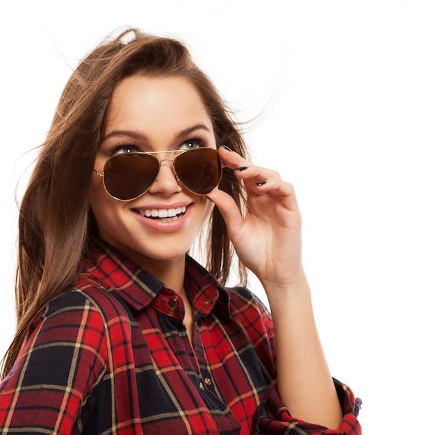 Młoda atrakcyjna kobieta w koszuli i okularach przeciwsłonecznych Darmowe Zdjęcia