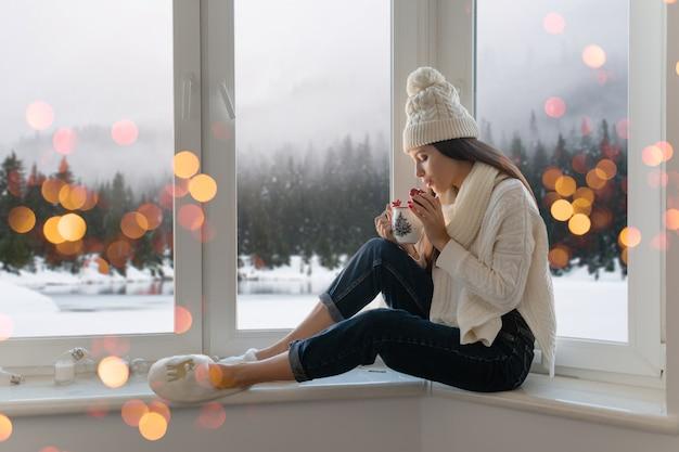 Młoda Atrakcyjna Kobieta W Stylowy Biały Sweter Z Dzianiny, Szalik I Czapka Siedzi W Domu Na Parapecie Na Boże Narodzenie Trzymając Kubek Pije Gorącą Herbatę, Zimowy Las W Tle, światła Bokeh Darmowe Zdjęcia