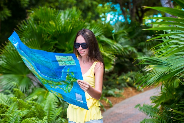 Młoda atrakcyjna kobieta z wielką mapą wyspy w dżungli Premium Zdjęcia