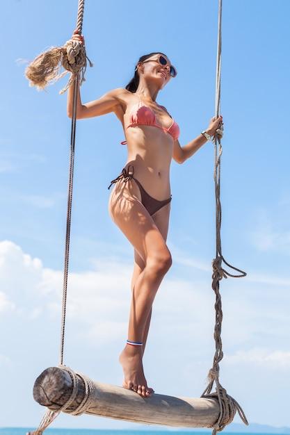 Młoda Atrakcyjna Seksowna Kobieta Na Wakacjach Siedzi Na Huśtawce Nad Morzem, Tropikalna Plaża, Chude Nogi, Podróżowanie Po Tajlandii, Uśmiechnięta, Szczęśliwa, Pozytywne Emocje, Letni Styl Darmowe Zdjęcia