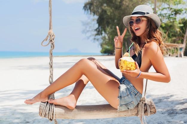 Młoda Atrakcyjna Seksowna Kobieta Na Wakacjach Siedzi Na Huśtawce Nad Morzem, Tropikalna Plaża, Pije Koktajl W Kokosie, Chude Nogi, Podróżuje Po Tajlandii, Uśmiechnięta, Szczęśliwa, Pozytywne Emocje, Letni Styl Darmowe Zdjęcia
