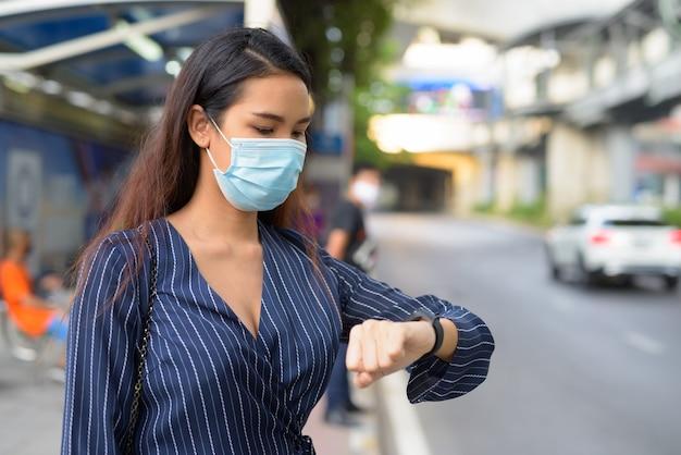 Młoda Azjatycka Bizneswoman Z Maską Sprawdza Smartwatch I Czeka Na Przystanku Autobusowym Premium Zdjęcia