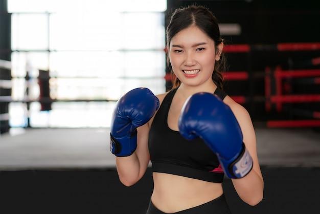 Młoda Azjatycka Bokserska Sprawności Fizycznej Kobieta Ono Uśmiecha Się Szczęśliwy Jest Ubranym Błękitne Bokserskie Rękawiczki Premium Zdjęcia
