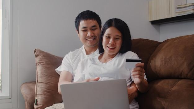 Młoda azjatycka ciężarna para robi zakupy online w domu. mama i tata czują się szczęśliwi, używając technologii laptopa i karty kredytowej kupując produkt dla dziecka, leżąc na kanapie w salonie w domu. Darmowe Zdjęcia