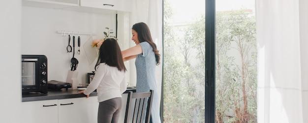 Młoda azjatycka japońska mama i córka gotuje w domu. styl życia kobiety szczęśliwe robi makaronowi i spaghetti wpólnie dla śniadaniowego posiłku w nowożytnej kuchni przy domem w ranku. Darmowe Zdjęcia