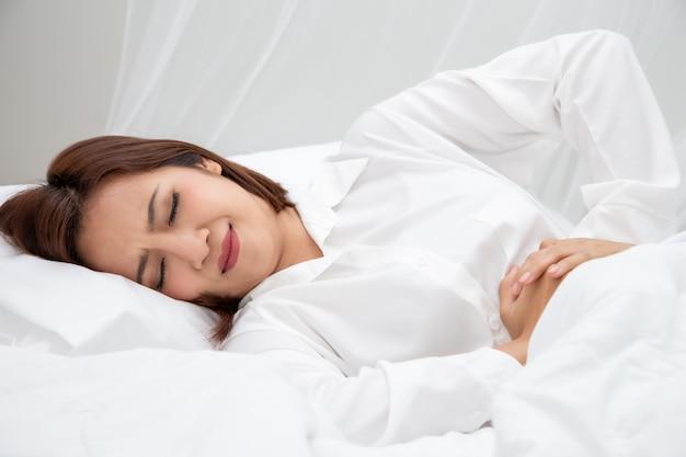 Młoda Azjatycka Kobieta Cierpi Na Ból Brzucha Lub Ból Brzucha Podczas Snu Na Białym łóżku W Domu Premium Zdjęcia