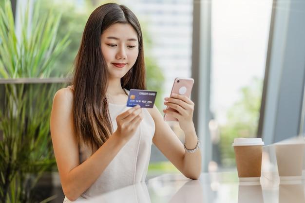 Młoda Azjatycka Kobieta Używa Kredytową Kartę Z Telefonem Komórkowym Dla Zakupy Online Premium Zdjęcia