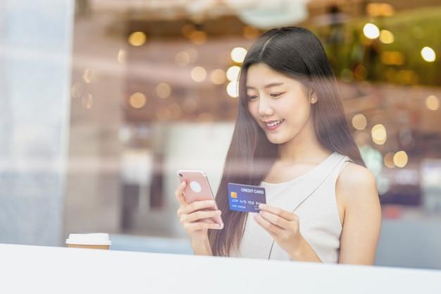 Młoda Azjatycka Kobieta Używa Kredytową Kartę Z Telefonem Komórkowym W Sklep Z Kawą Premium Zdjęcia