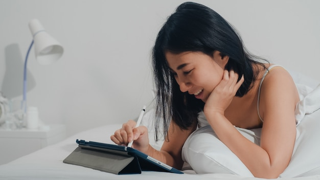 Młoda azjatycka kobieta używa pastylkę sprawdza ogólnospołecznego medialnego czuje szczęśliwy ono uśmiecha się podczas gdy kłamający na łóżku po budził się przy domem w ranku, atrakcyjny indyjski żeński ono uśmiecha się relaksuje w sypialni w domu. Darmowe Zdjęcia