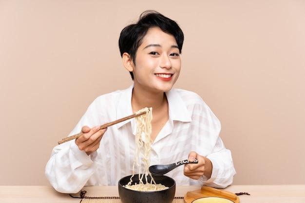 Młoda Azjatycka Kobieta W Stole Z Pucharem Kluski Premium Zdjęcia