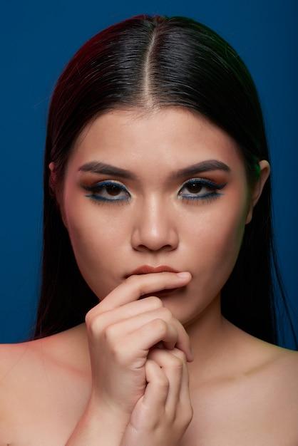 Młoda Azjatycka Kobieta Z Pełnym Makeup I Nagimi Ramionami Dotyka Wargi I Patrzeje Kamerę Darmowe Zdjęcia