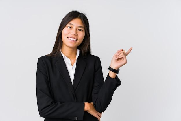 Młoda Azjatykcia Biznesowa Kobieta Ono Uśmiecha Się Radośnie Wskazujący Z Palcem Wskazującym Daleko Od. Premium Zdjęcia