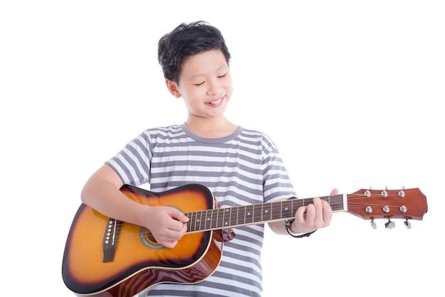Młoda Azjatykcia Chłopiec Bawić Się Gitarę I Uśmiechy Nad Białym Tłem Premium Zdjęcia