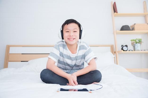 Młoda Azjatykcia Chłopiec Jest Ubranym Słuchawki Słuchającą Muzykę Premium Zdjęcia