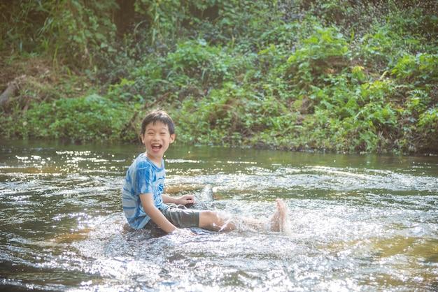 Młoda Azjatykcia Chłopiec Ono Uśmiecha Się Podczas Gdy Palying W Rzece Premium Zdjęcia
