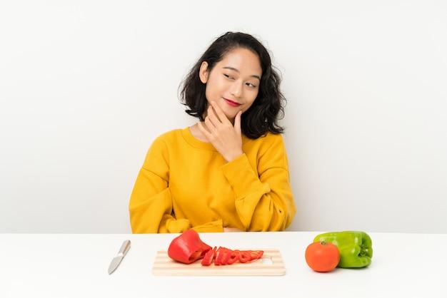 Młoda Azjatykcia Dziewczyna Myśleć Pomysł Z Warzywami W Stole Premium Zdjęcia