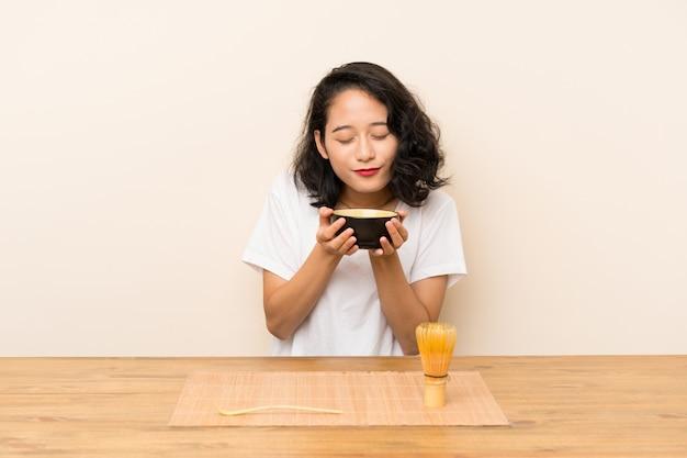 Młoda azjatykcia dziewczyna z herbacianą matcha Premium Zdjęcia
