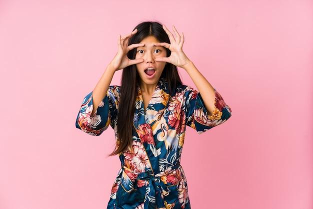 Młoda Azjatykcia Kobieta Jest Ubranym Piżamę Kimono I Utrzymuje Oczy Otwarte, Aby Znaleźć Szansę Na Sukces. Premium Zdjęcia