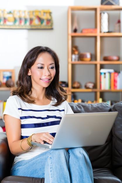 Młoda azjatykcia kobieta na kanapie w domu Premium Zdjęcia