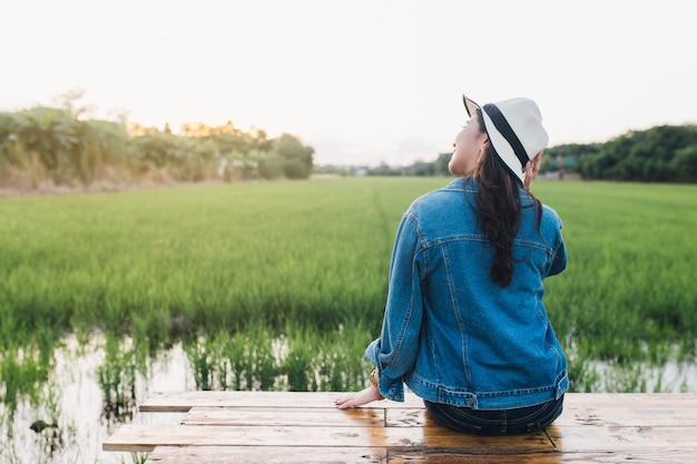 Młoda Azjatykcia Kobieta Ono Uśmiecha Się W Kapeluszu. Dziewczyna Cieszy Się Przy Piękną Naturą Z Zmierzchem. Premium Zdjęcia