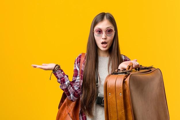 Młoda azjatykcia kobieta trzyma walizkę imponującą mienie kopii przestrzeń na palmie. Premium Zdjęcia