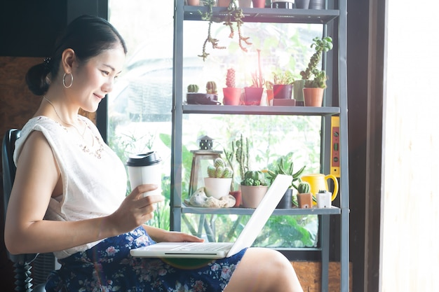 Młoda azjatykcia kobieta używa laptop i pijący kawę w kawiarni Premium Zdjęcia