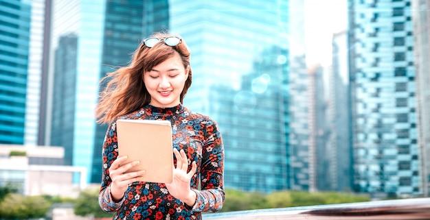 Młoda Azjatykcia Kobieta Używa Urządzenie Elektroniczne W Nowożytnym Mieście Premium Zdjęcia
