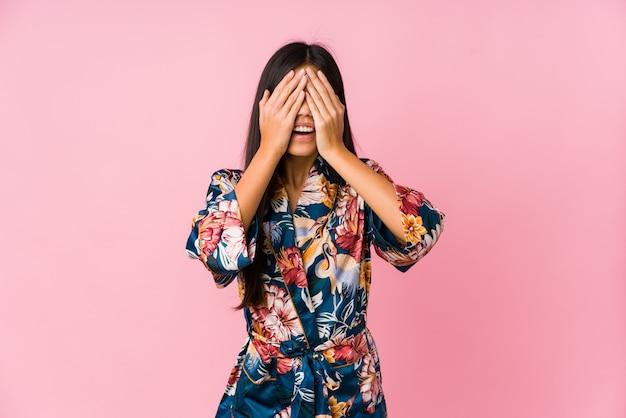Młoda Azjatykcia Kobieta W Piżamie Kimono Zakrywa Oczy Dłońmi, Uśmiecha Się Szeroko Czekając Na Niespodziankę. Premium Zdjęcia