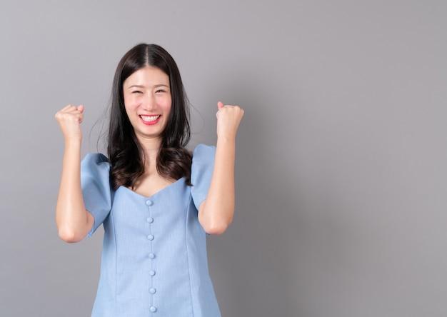 Młoda Azjatykcia Kobieta Z Szczęśliwą I Podekscytowaną Twarzą Na Szarość Premium Zdjęcia